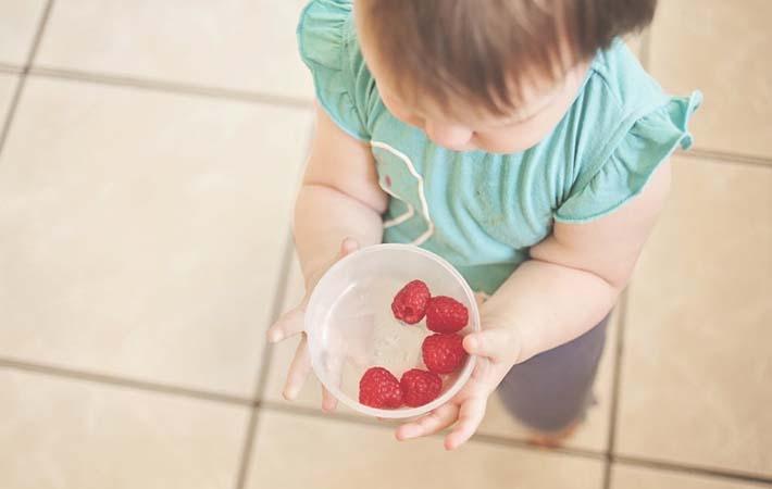 Niña con comida sana para evitar la obesidad infantil